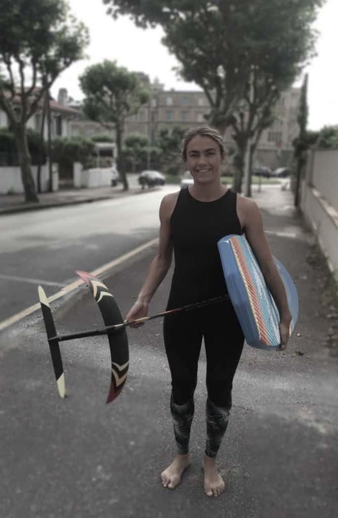 C'est une photo de la surfeuse Lea Brassy tenant en main le surf-foil Sroka.