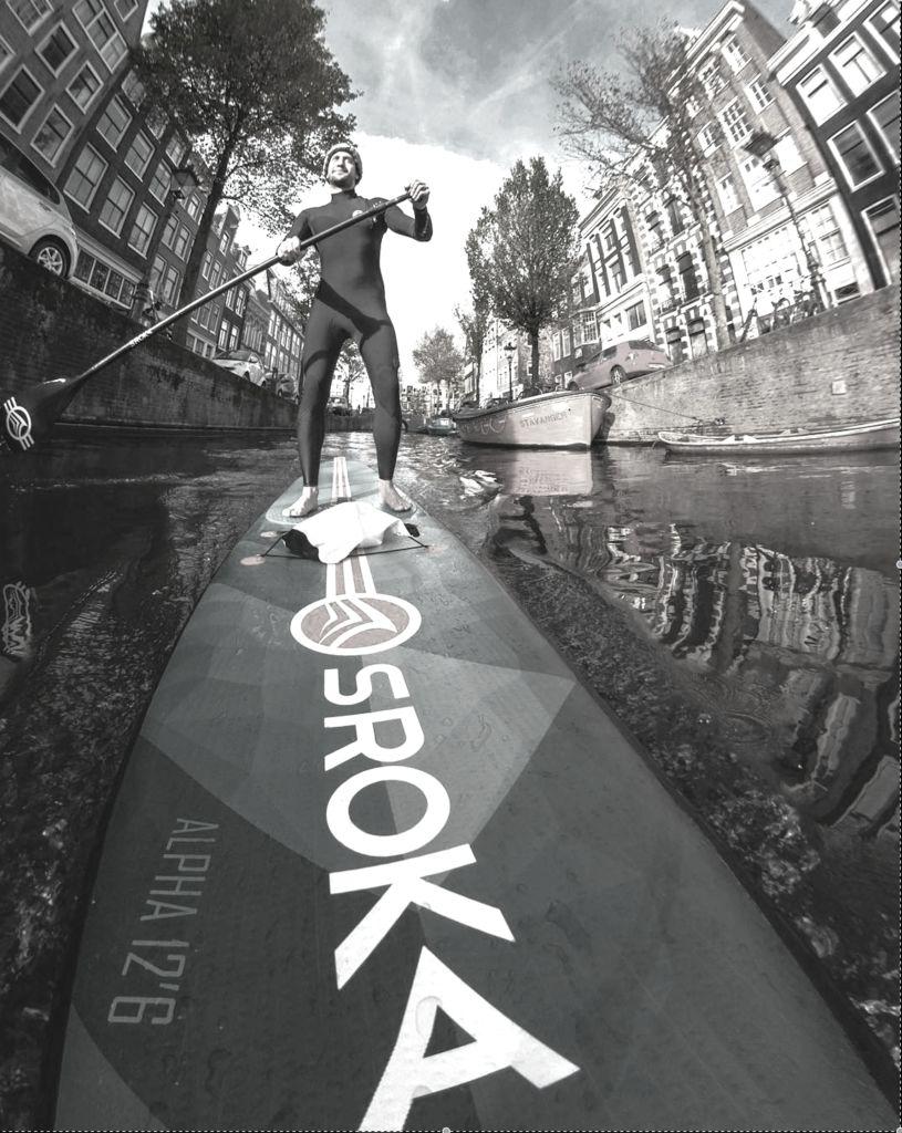 Romain réalise des images en vidéo et photo. Il ride l'Alpha, un paddle gonflable Sroka dans les canaux d'Amsterdam.